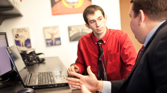 Young professional speaking with adult professional in front of laptop