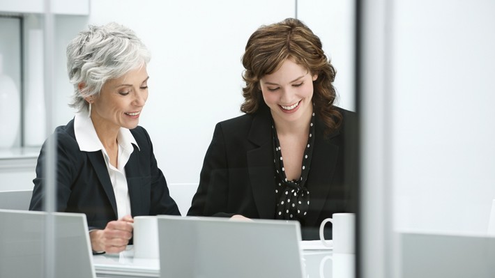 Two professional women work together at a desk