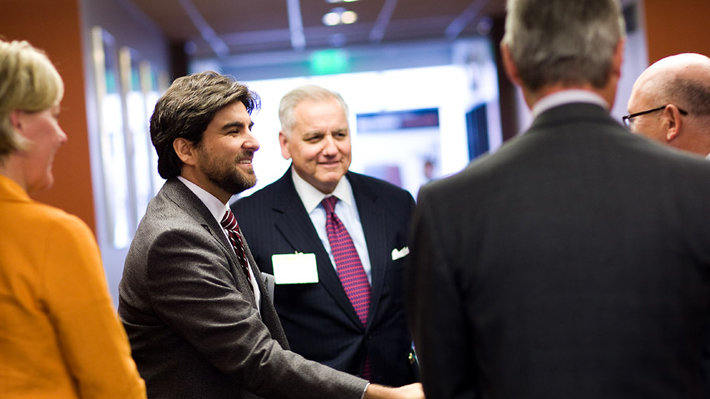 Faculty member shakes hand with industry leaders