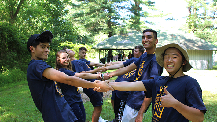 Students pose for a photo during a ropes course outside