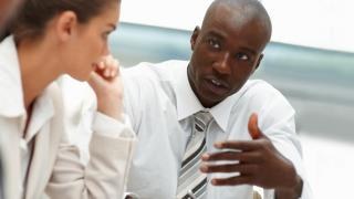 Businessman and businesswoman discuss during meeting