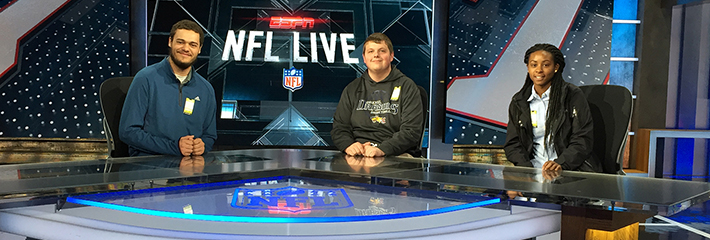 SMT students pose at NFL reporting desk