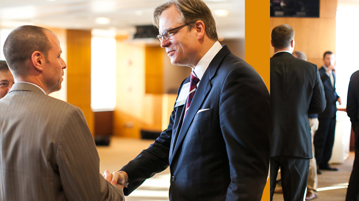 Alumnus shaking hands with an MBA student