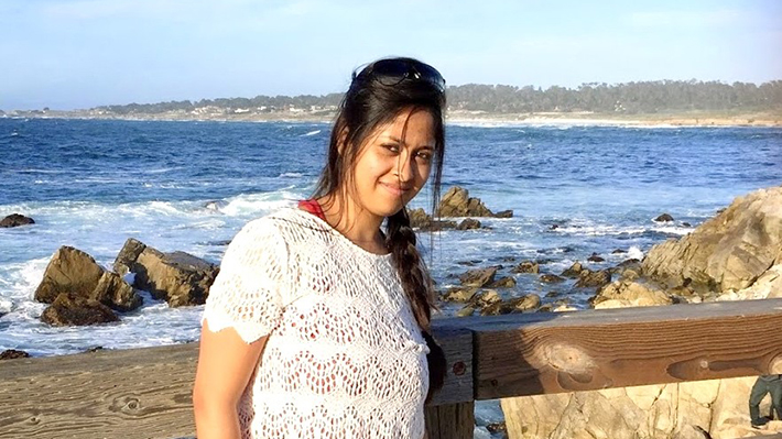 Roshmika Chandra stands in front of a rocky beach