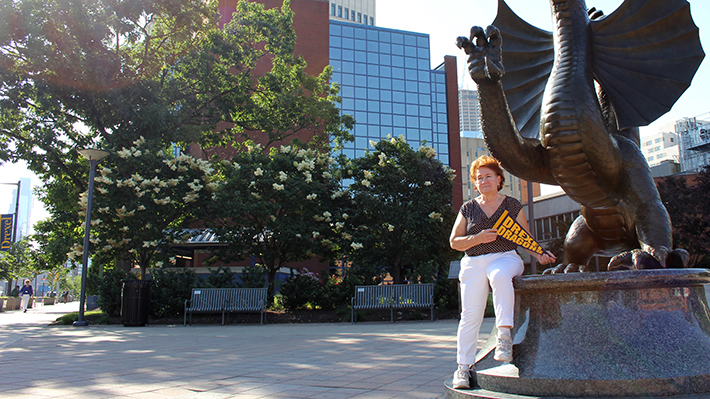 Bernardine Rzucidlo  in front of dragon statue