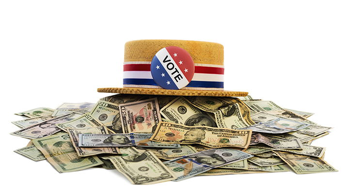 Vote button on hat sitting on a pile of money