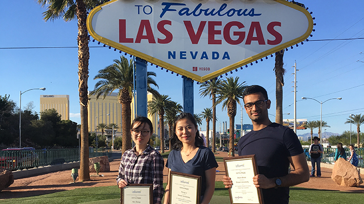 Arjun Arora, Hong Li and Ran Zhang in front of Las Vegas sign