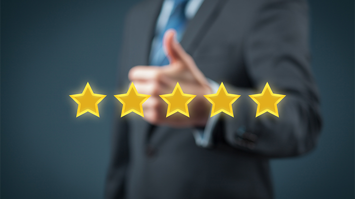 A man stands behind a five star rating