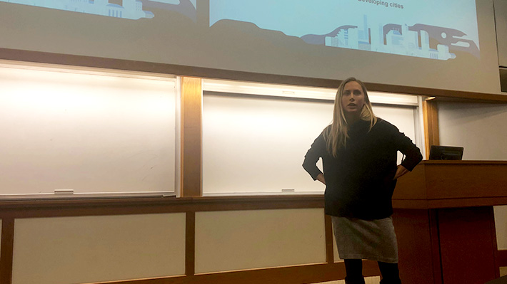 Female representative from Uber stands near podium presenting