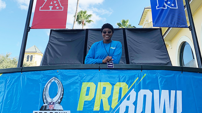 Arian Palmer stands behind Pro Bowl sign