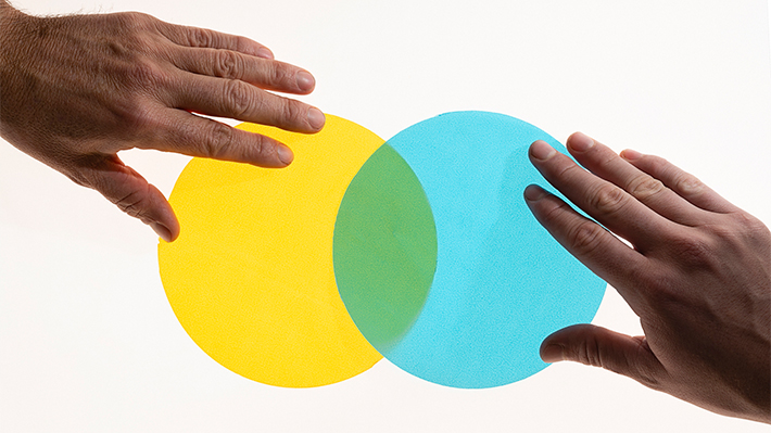 Two hands positioning yellow and blue circles into a Venn diagram