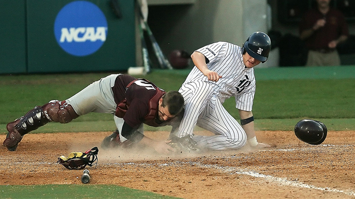 A baseball player slides into home plate near the opposing team's catcher