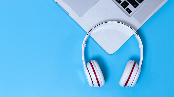 Headphones and laptop against a light blue background