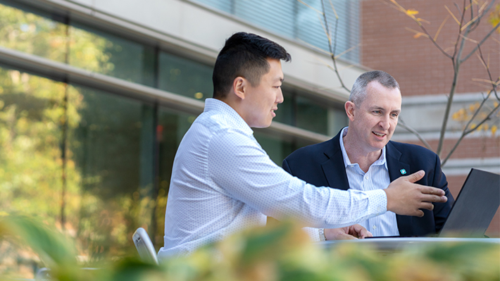 Two businessmen conversing and viewing a laptop screen outside