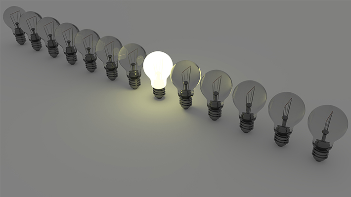 A row of lightbulbs, only one near the middle is lit